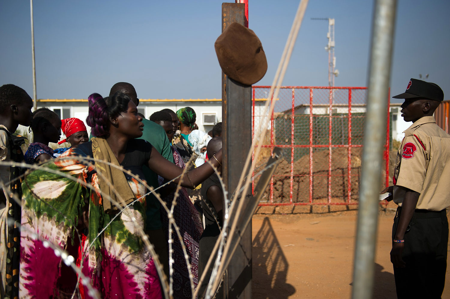 People stand at the gates of a spontaneous camp for internally displaced persons at the United Nations Mission to South Sudan base in Juba, South Sudan, on Jan. 9, 2014. Over 17,000 people are living at the base, with new arrivals every day, due to ongoing conflict in the world's youngest nation.