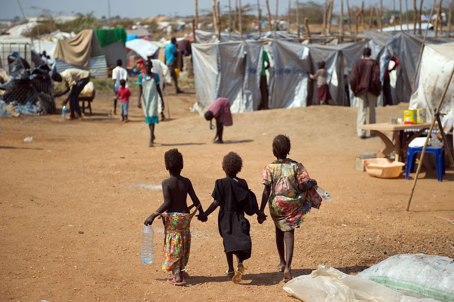 Three children walk through a spontaneous camp for internally displaced persons at the United Nations Mission to South Sudan base in Juba,  on Jan. 9, 2014.