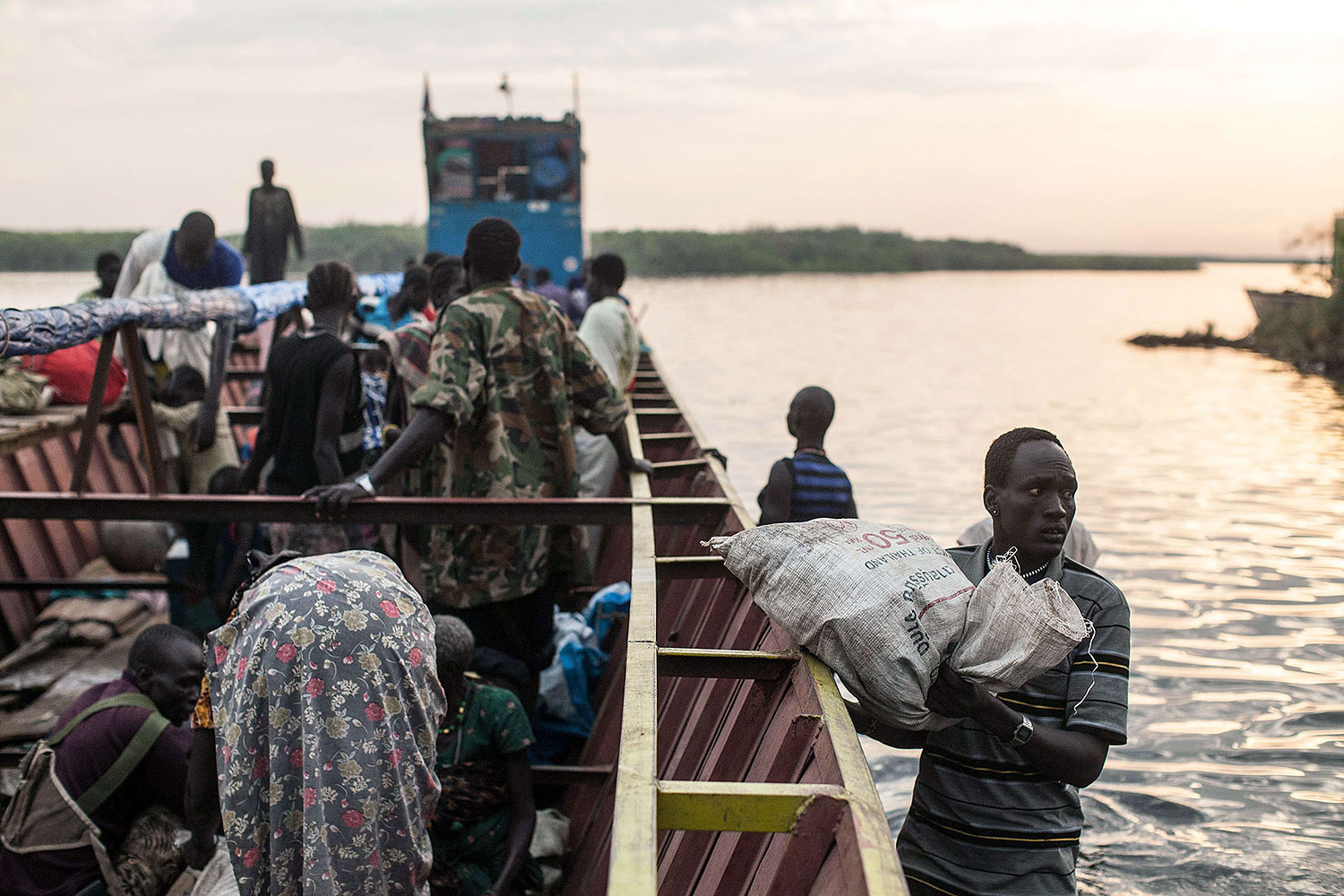 People unload the few belongings on Jan. 9, 2014 at Minkammen, South Sudan that they were able to bring with them to the camps.
