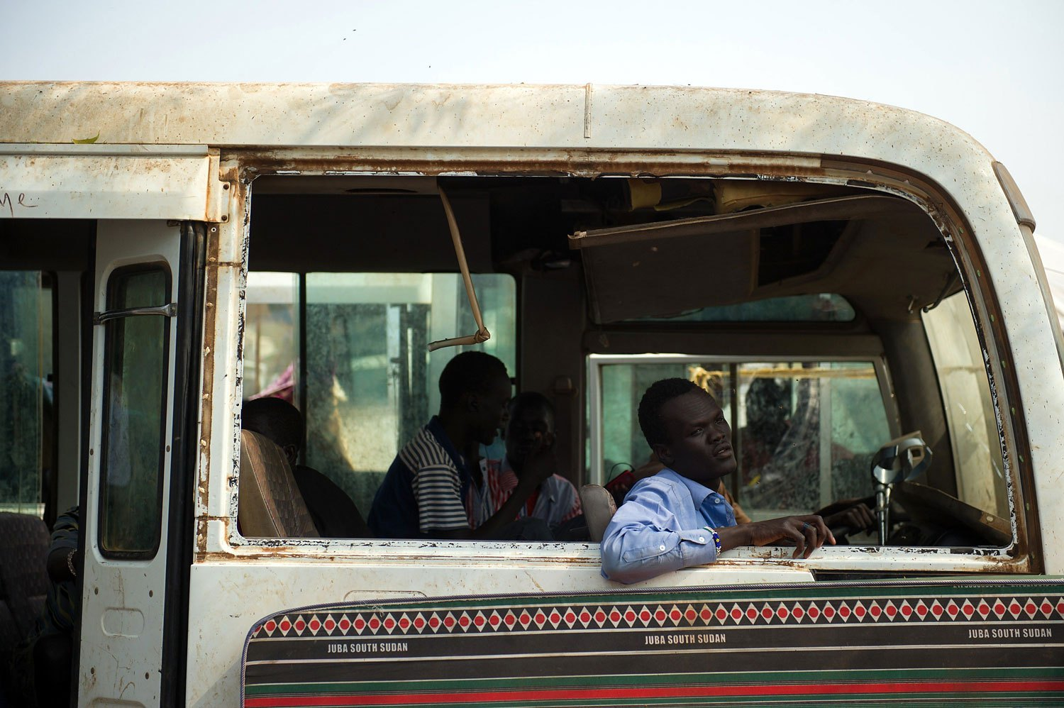 A South Sudanese man sits in the shell of an old bus in a spontaneous camp for internally displaced persons at the United Nations Mission to South Sudan base in Juba, South Sudan, on Jan. 9, 2014.