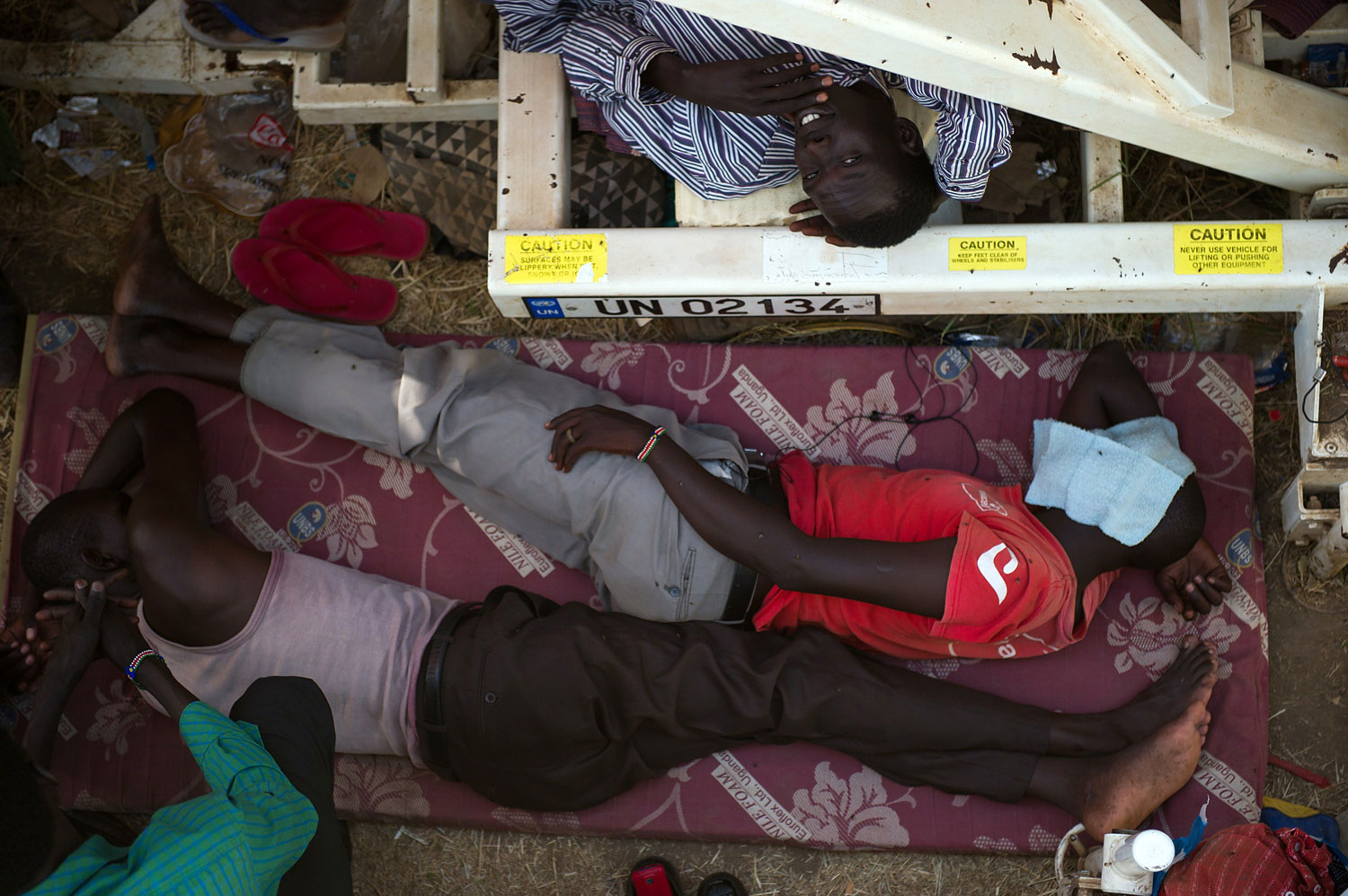 South Sudanese men lay down between makeshift shelters in a spontaneous camp for internally displaced persons at the United Nations Mission to South Sudan base in Juba, South Sudan, on Jan. 9, 2014.