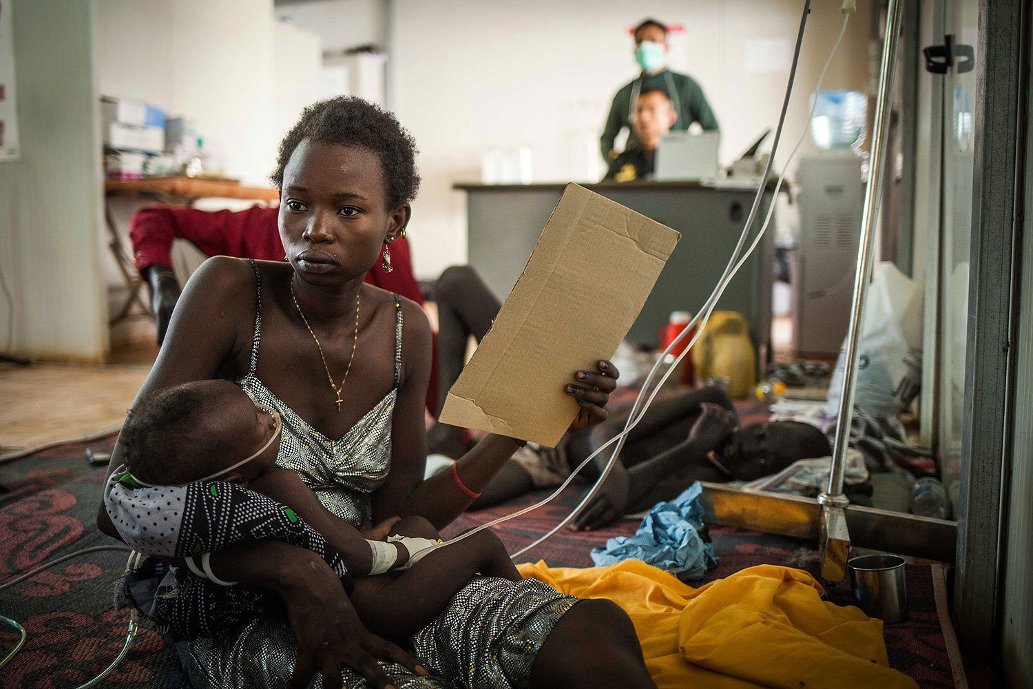 A woman holds her child receiving treatment at a makeshift clinic at an internally displaced persons' camp run by the United Nations in Juba on Jan. 7, 2014.