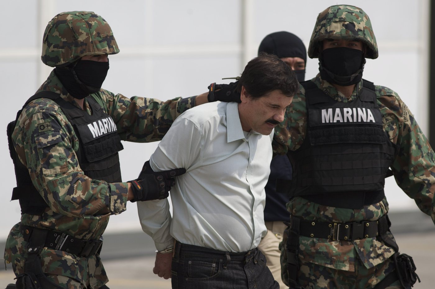 Joaquin  El Chapo  Guzman is escorted to a helicopter in handcuffs by Mexican marines at a navy hanger in Mexico City, on Feb. 22, 2014.