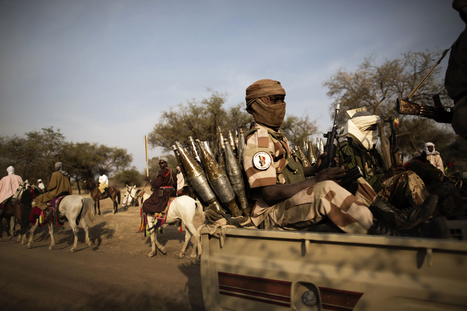Chadian soldiers escorting the Chadian President, speed past horsemen arriving to attend a ceremony marking the 50th anniversary of the Zakouma National Park, Chad's oldest natural park, during which elephant tusks will be incinerated, Feb. 21, 2014.