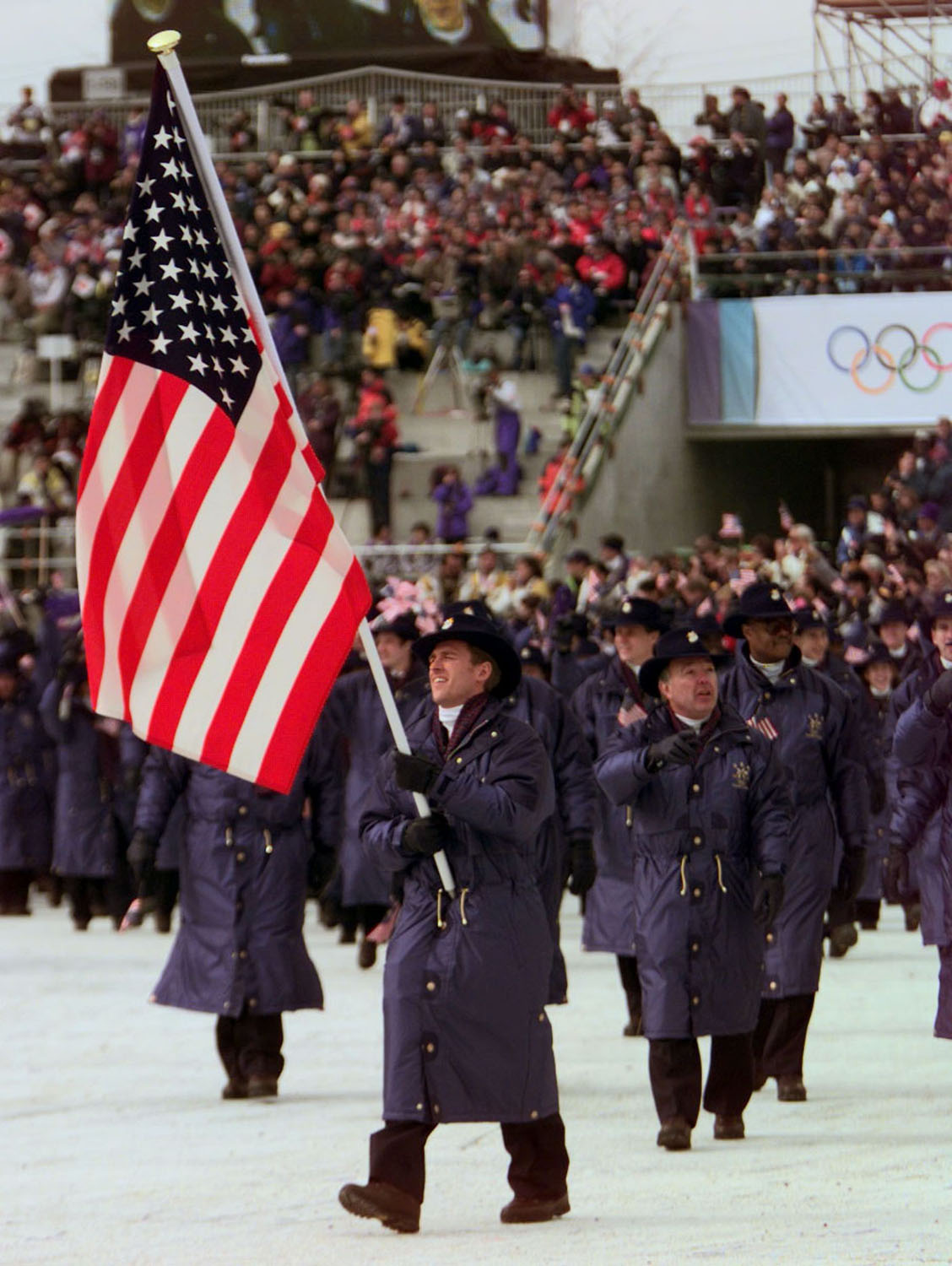 Four-time Olympic speed skater Eric Flaim carries the United States flag into the Olympic Stadium in Nagano, Japan, as he leads his team into the 1998 Winter Olympic Games opening ceremony.