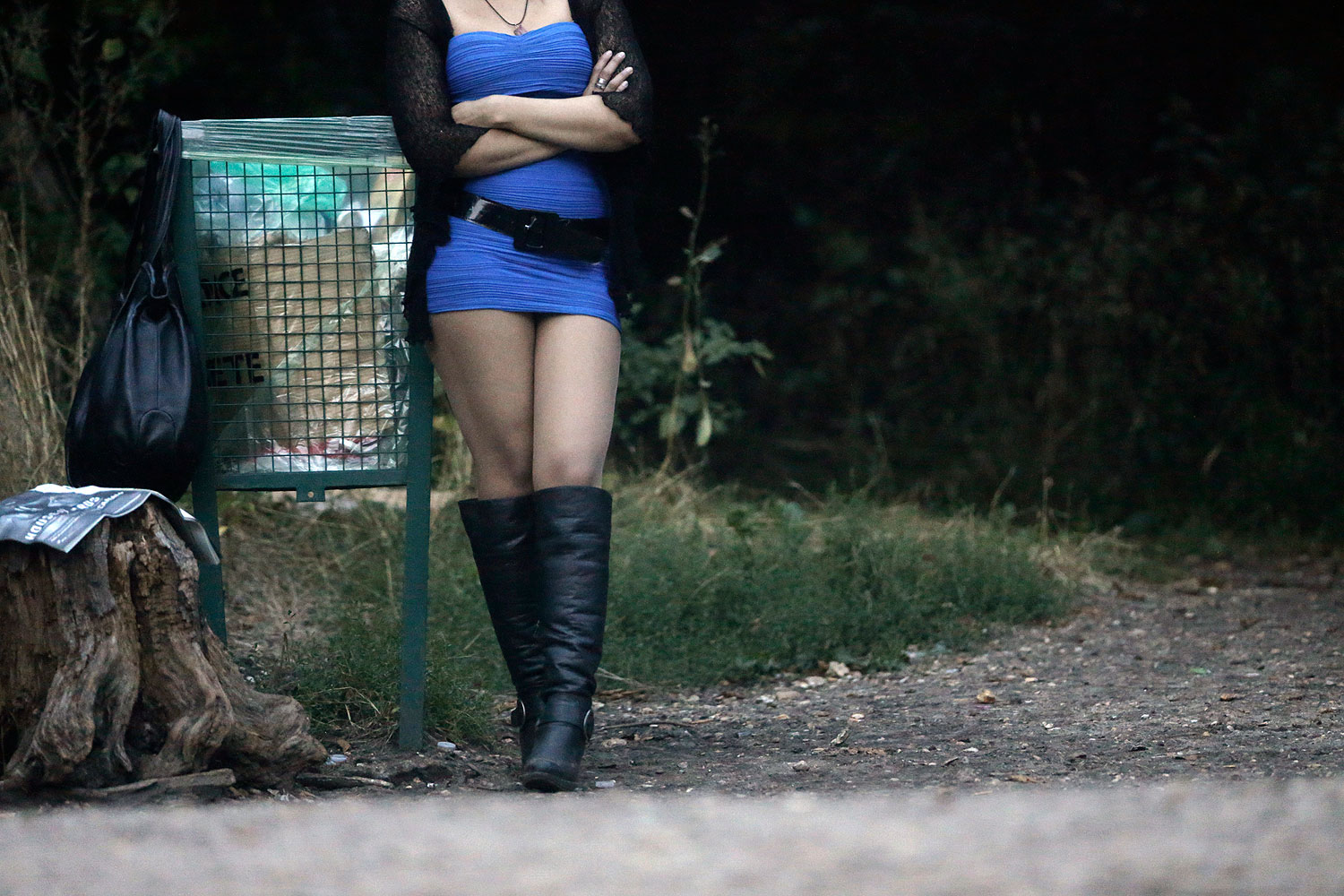 A prostitute waits for customers along a road of the Bois de Boulogne in Paris Aug. 28, 2013