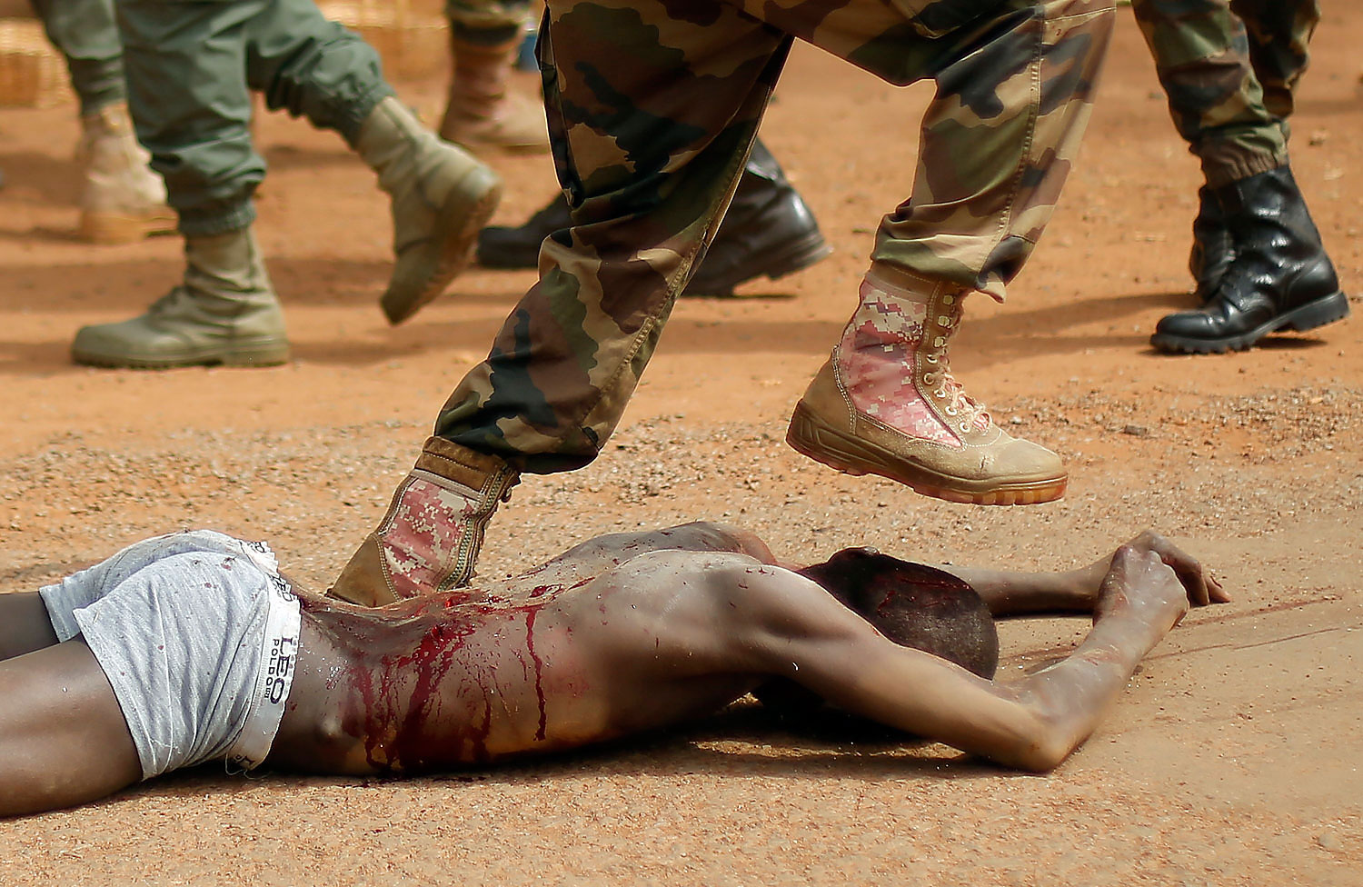 A Central African Armed Forces officer jumps on the lifeless body of a suspected Muslim Seleka militiaman moments after Central African Republic Interim President Catherine Samba-Panza addressed the troops in Bangui, Feb. 5, 2014.