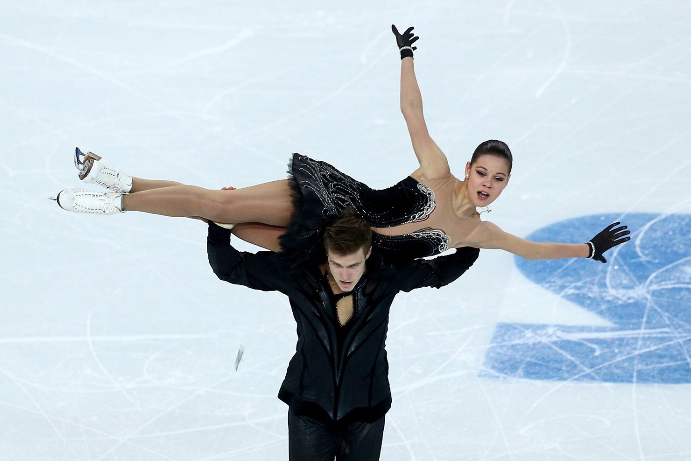 The blur on the left is a feather falling from Russia's Elena Ilinykh's costume as she and partner Nikita Katsalapov compete in the team skating event during day two of the Sochi 2014 Winter Olympics. The ice dancers lost a point for the wardrobe malfunction.