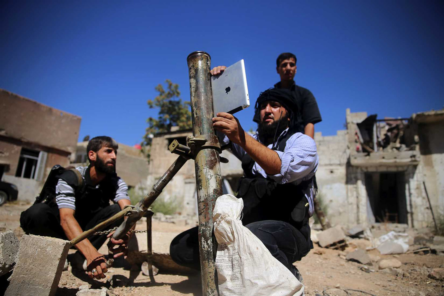 A rebel fighter, who belongs to the Free Syrian Army, uses an iPad during preparations to fire a homemade mortar at a battlefront in Damascus on Sept. 15, 2013