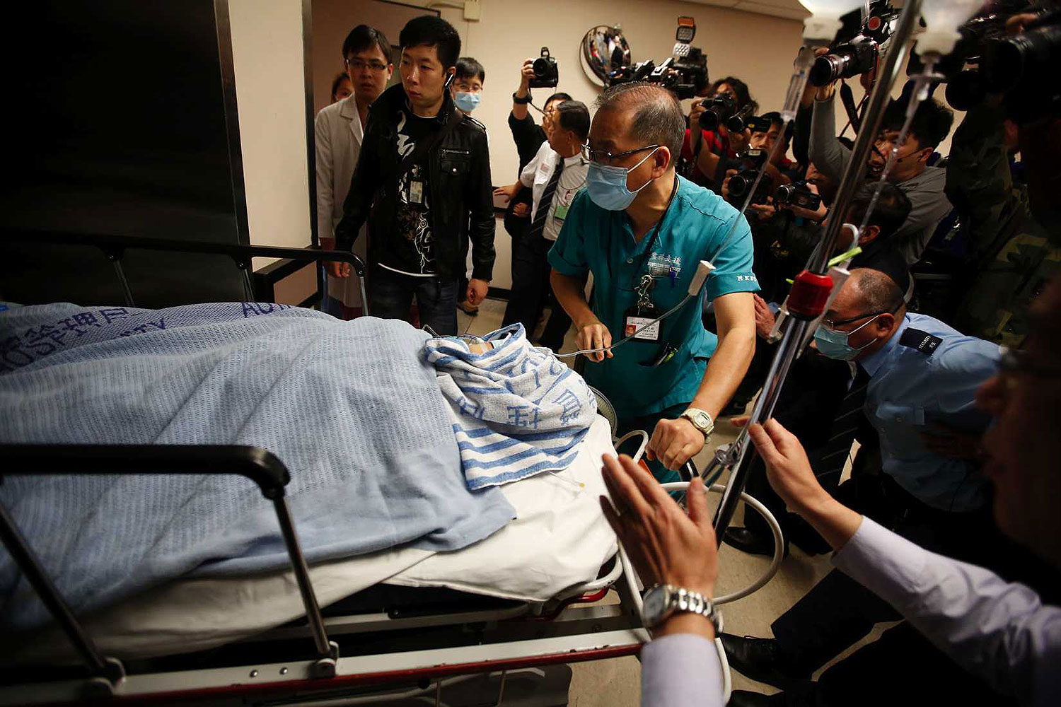 Former Ming Pao chief editor Kevin Lau Chun-to is wheeled into the operation theatre at a hospital in Hong Kong Feb. 26, 2014