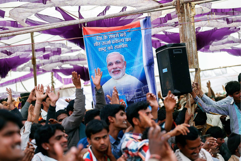 Supporters cheer beneath a poster featuring Narendra Modi at a rally near Bhagwanpura, Madhya Pradesh, India, on Feb. 26, 2014