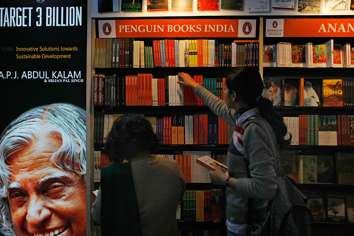 Indian women browse through Penguin edition books on display at the New Delhi World Book Fair in New Delhi in 2012