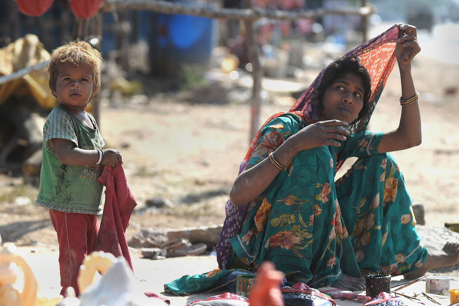 An Indian labourer sits with a child outside a makeshift shelter on a highway on the outskirts of Hyderabad on Nov. 14, 2013