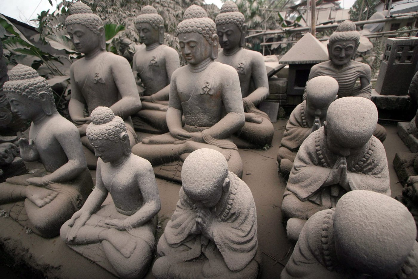 Buddha statues are covered with volcanic ash from the Mount Kelud volcano eruption at a shop in Magelang, Central Java, Feb. 14, 2014.
