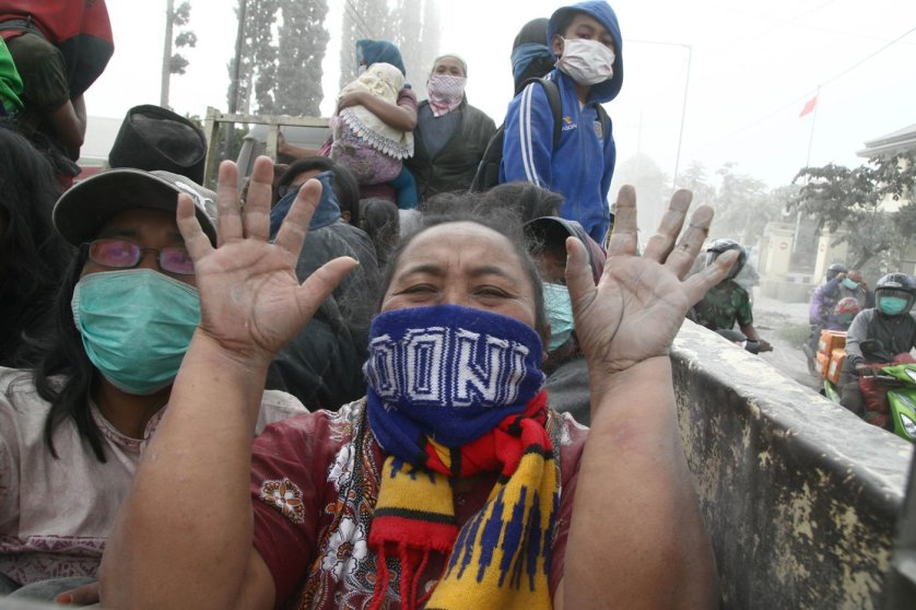 A woman gestures during the evacuation in Malang, East Java province, on Feb. 14, 2014 moments after Mount Kelud's eruption.