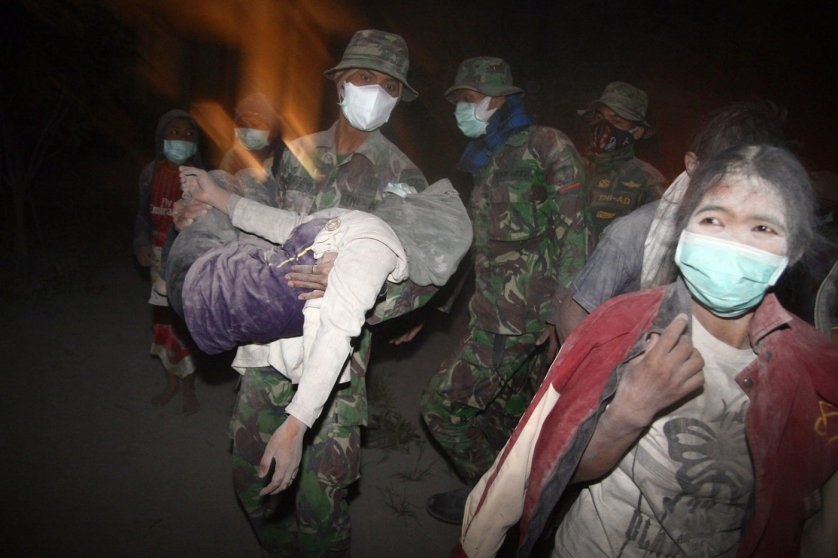 Indonesian soldiers evacuate ash covered residents in Malang, East Java province on Feb. 14, 2014 moments after Mount Kelud, considered one of the most dangerous volcanoes on densely populated Java, erupted.