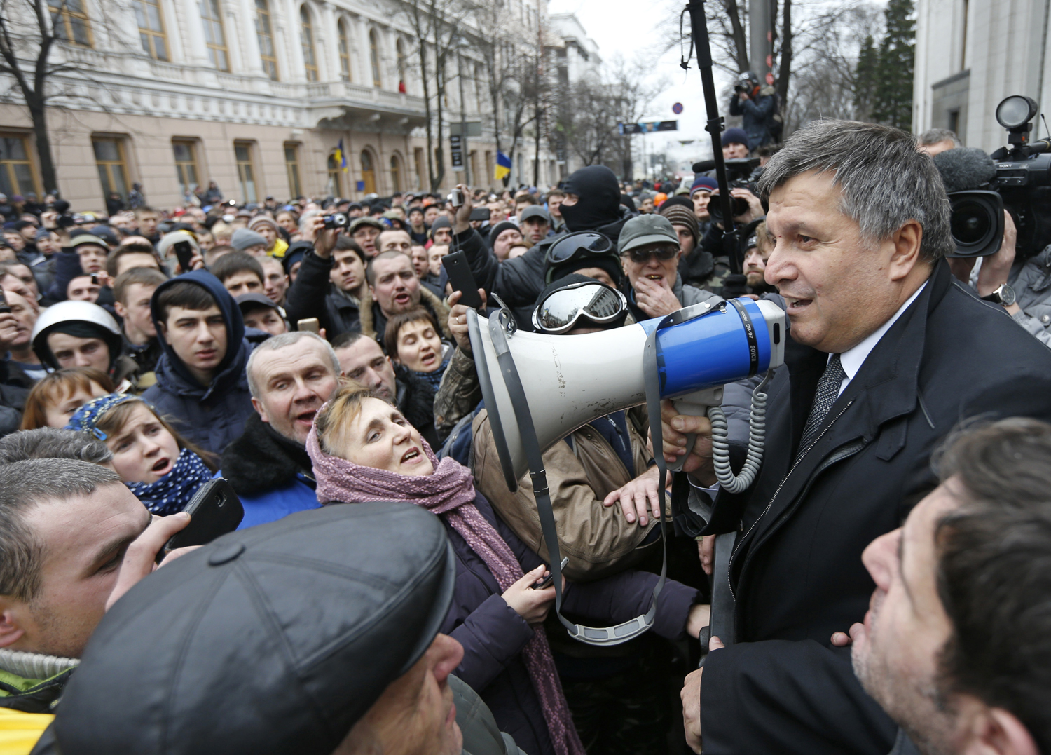 Newly elected Ukrainian interior minister Arsen Avakov (R) holds a loud-speaker as he addresses anti-government protesters outside the Ukrainian parliament building in Kiev February 22, 2014.