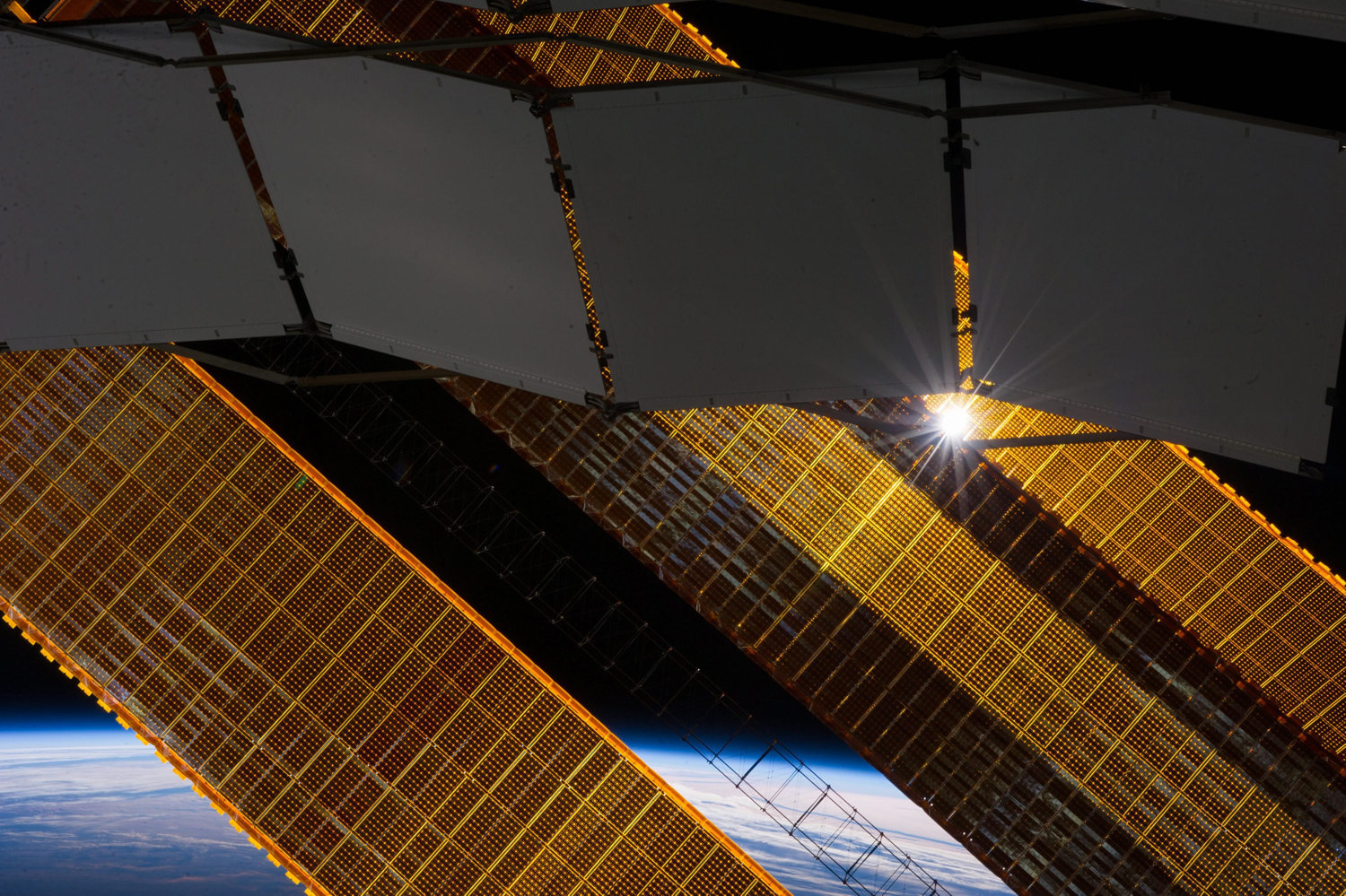 The sun shines through a radiator and a solar array panel on the International Space Station (ISS) in this photograph taken by a crew member on Jan. 2, 2014.