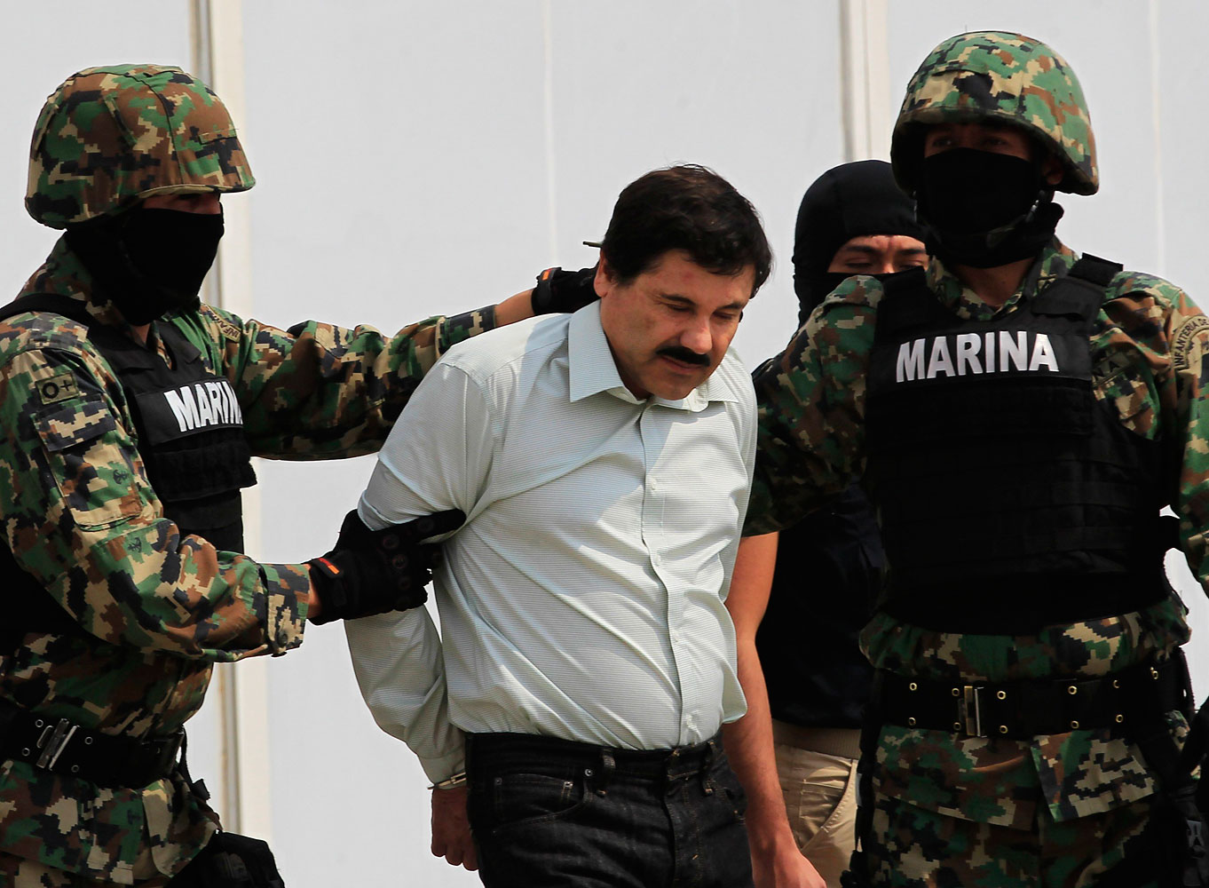 Joaquin  Shorty  Guzman is escorted by soldiers during a presentation at the Navy's airstrip in Mexico City Feb. 22, 2014.
