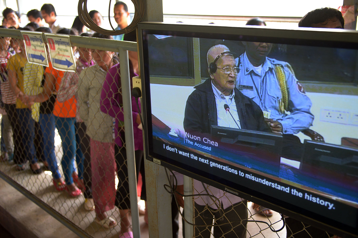 Former Cambodian Khmer Rouge leader  Brother Number Two  Nuon Chea is seen on a television screen (R) as people (L) line up to attend the trial of former Khmer Rouge leaders at the Extraordinary Chamber in the Courts of Cambodia (ECCC) in Phnom Penh in Oct. 2013