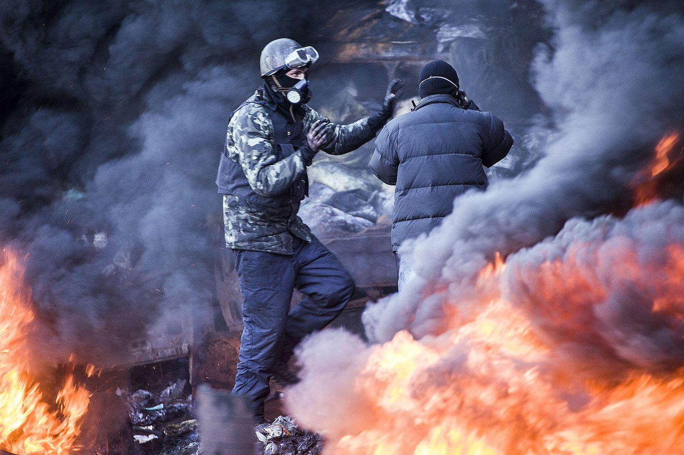 Anti-government demonstrators stand among the smoke of burning barricades during clashes with riot police in Kiev, February 18, 2014.