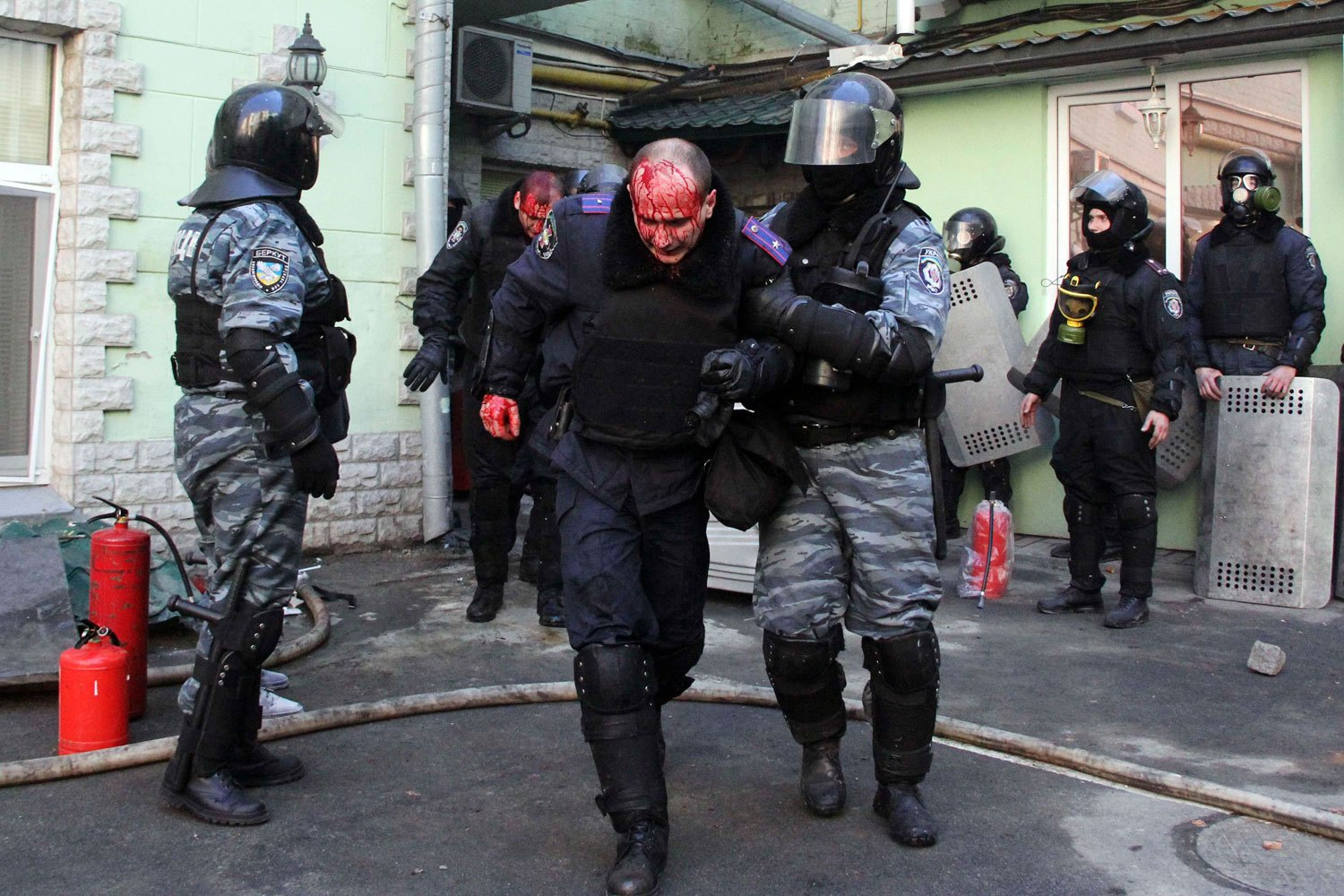 Interior Ministry members injured during clashes with anti-government protesters are escorted by colleagues in Kiev, on Feb. 18, 2014.