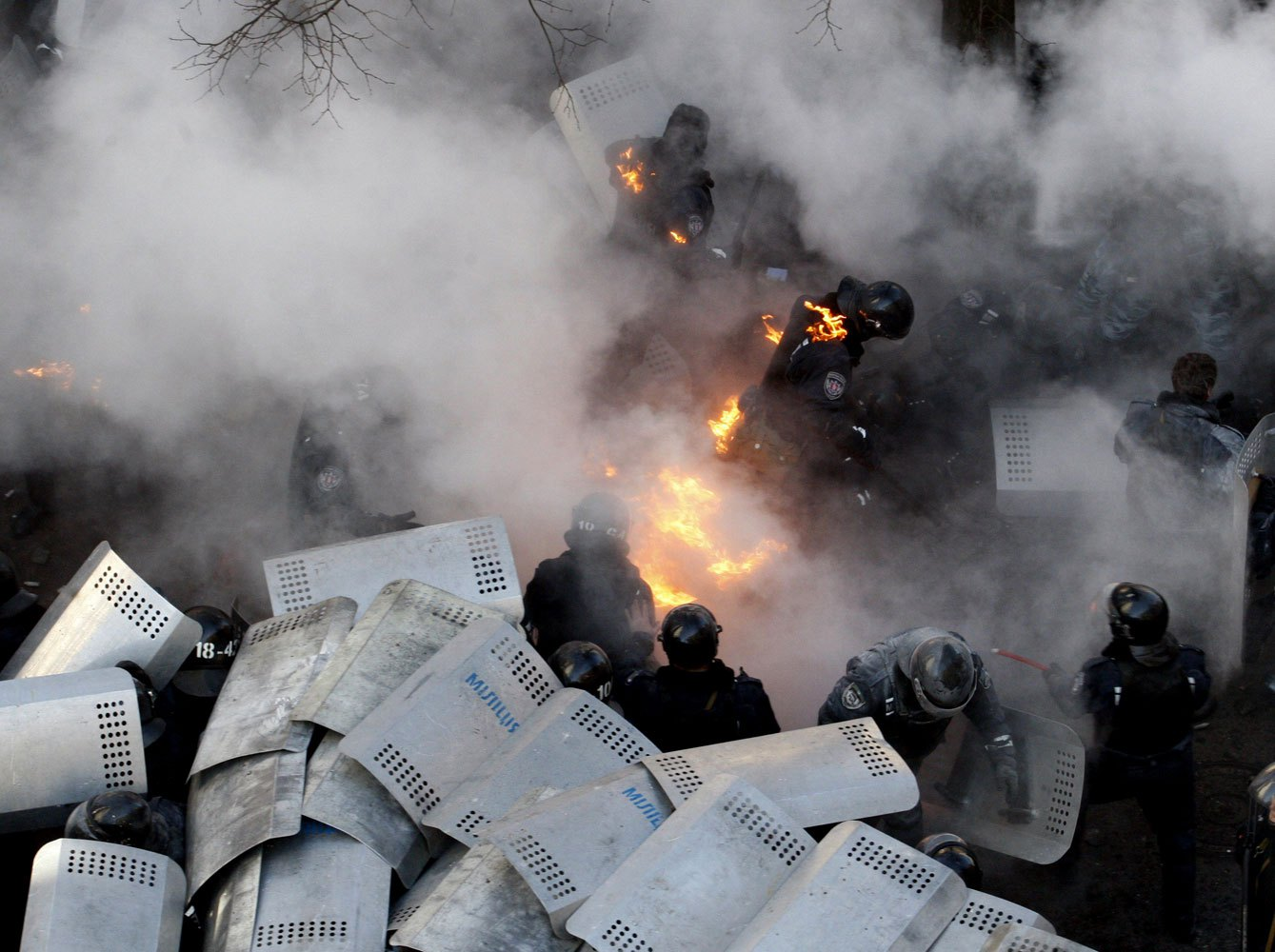 Policemen run amid flames during clashes with anti-government protesters in front of the Ukrainian Parliament in Kiev, on Feb. 18, 2014.
