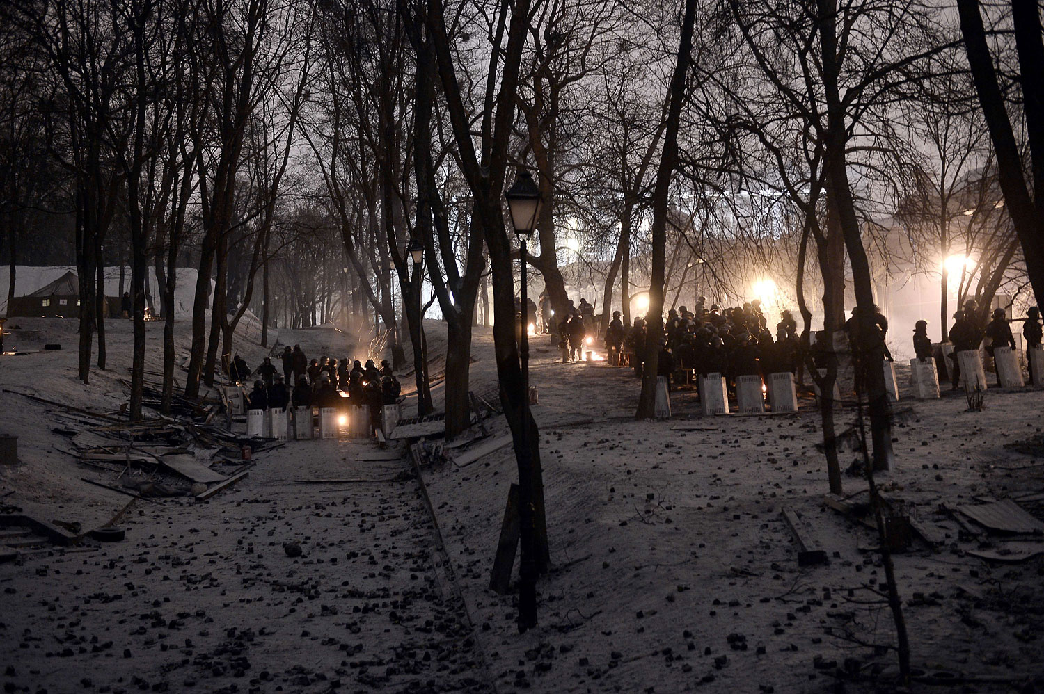 Riot police stand guard opposite anti-government protesters in a park area near a road block in Kiev on Jan. 28, 2014.