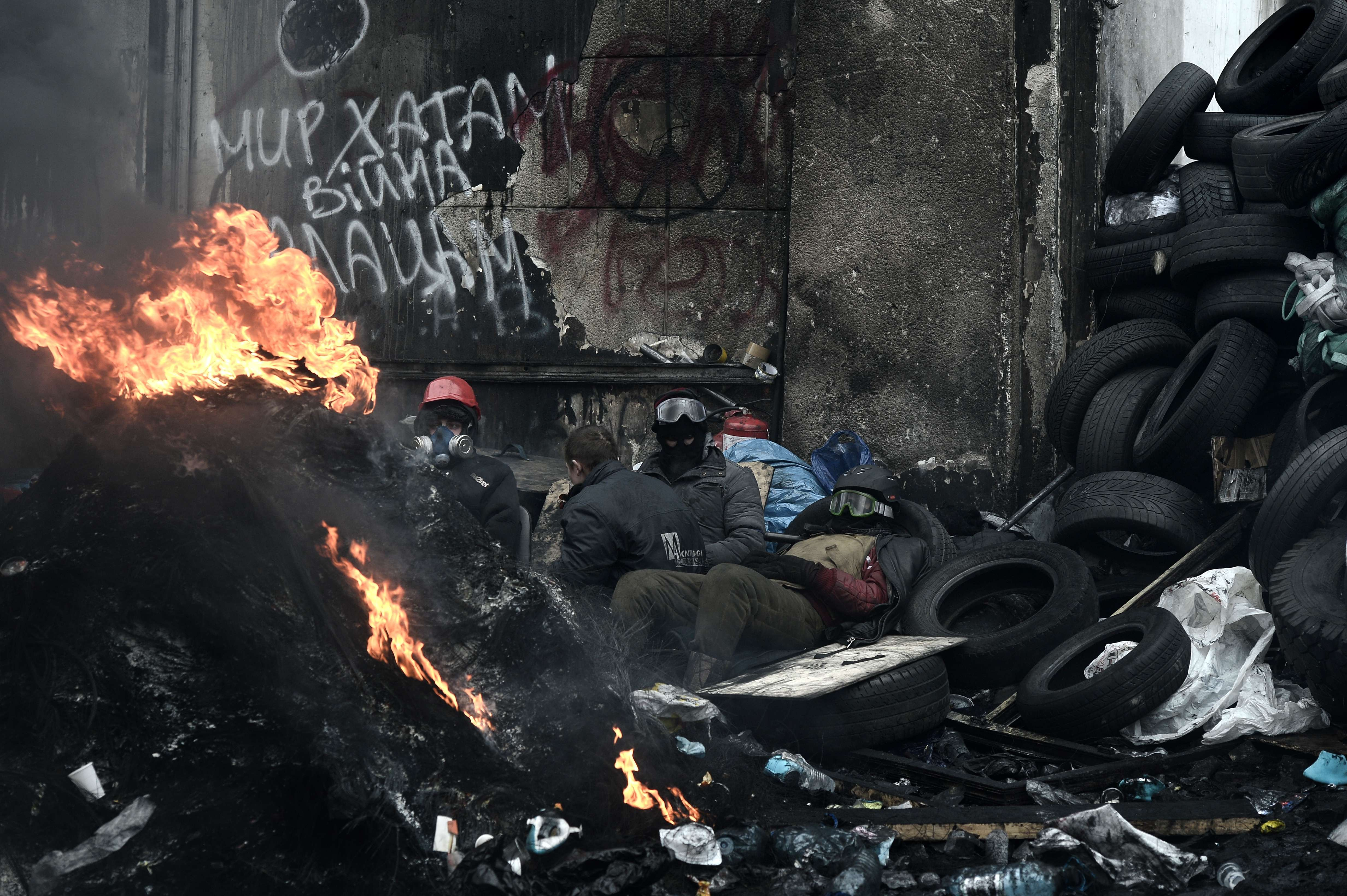 A anti-government protesters rest near a fire next to a road block in Kiev on Jan. 28, 2014.