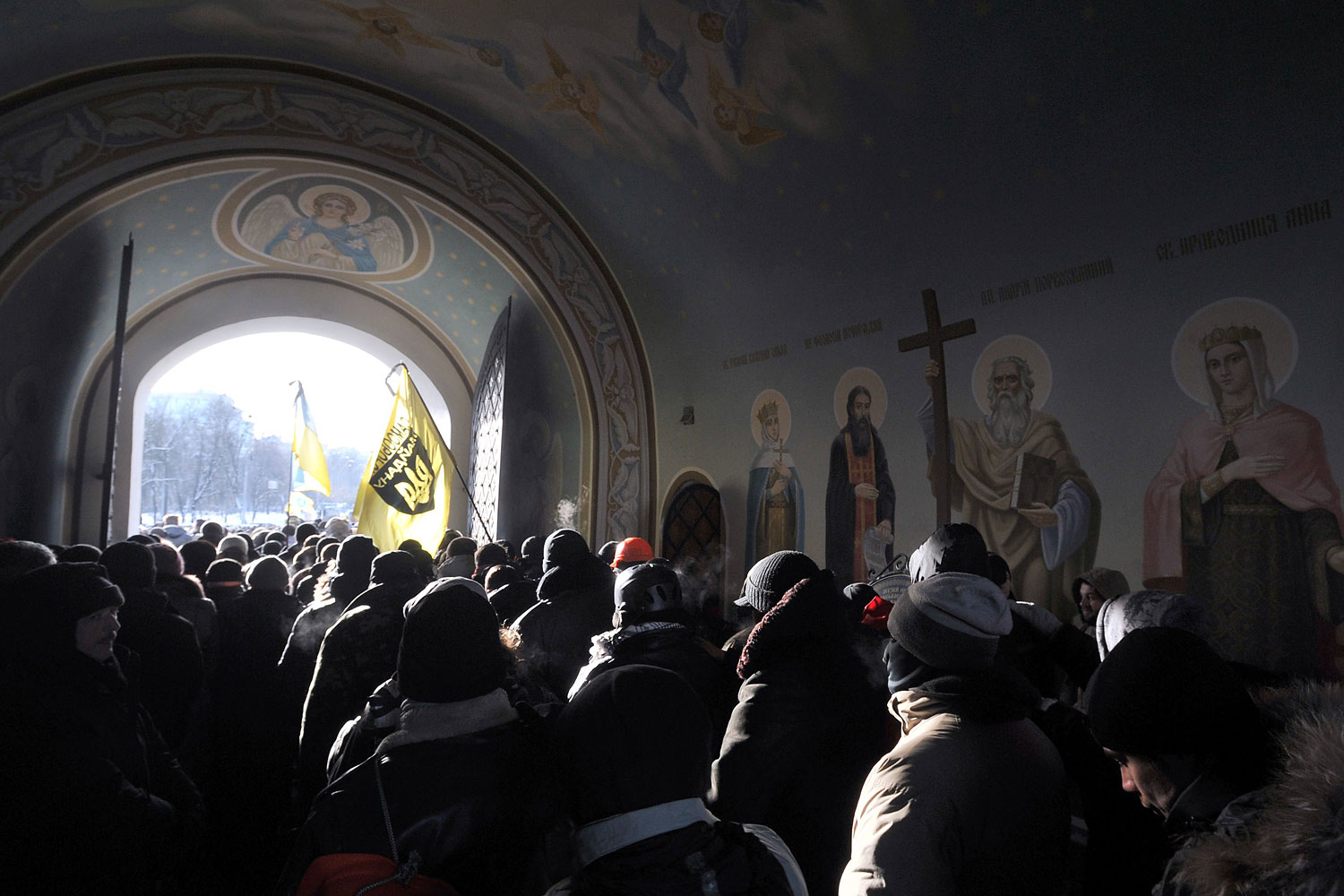 Ukrainian protesters hold their flags outside of Mikhaylovsky Cathedral as they pay their final respects to Belarussian protester Mikhail Zhiznevsky during a funeral service in Kiev on Jan. 26, 2014.