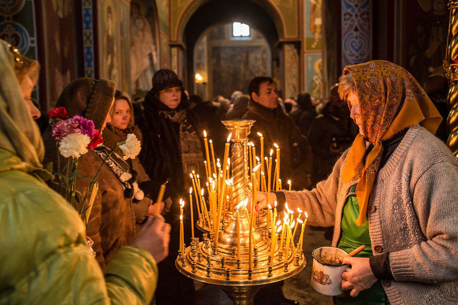 Women light candles inside Mikhailovsky Cathedral before a memorial service for Mikhail Zhiznevsky, 25, an anti-government protester who was killed in clashes with police on January 26, 2014 in Kiev.