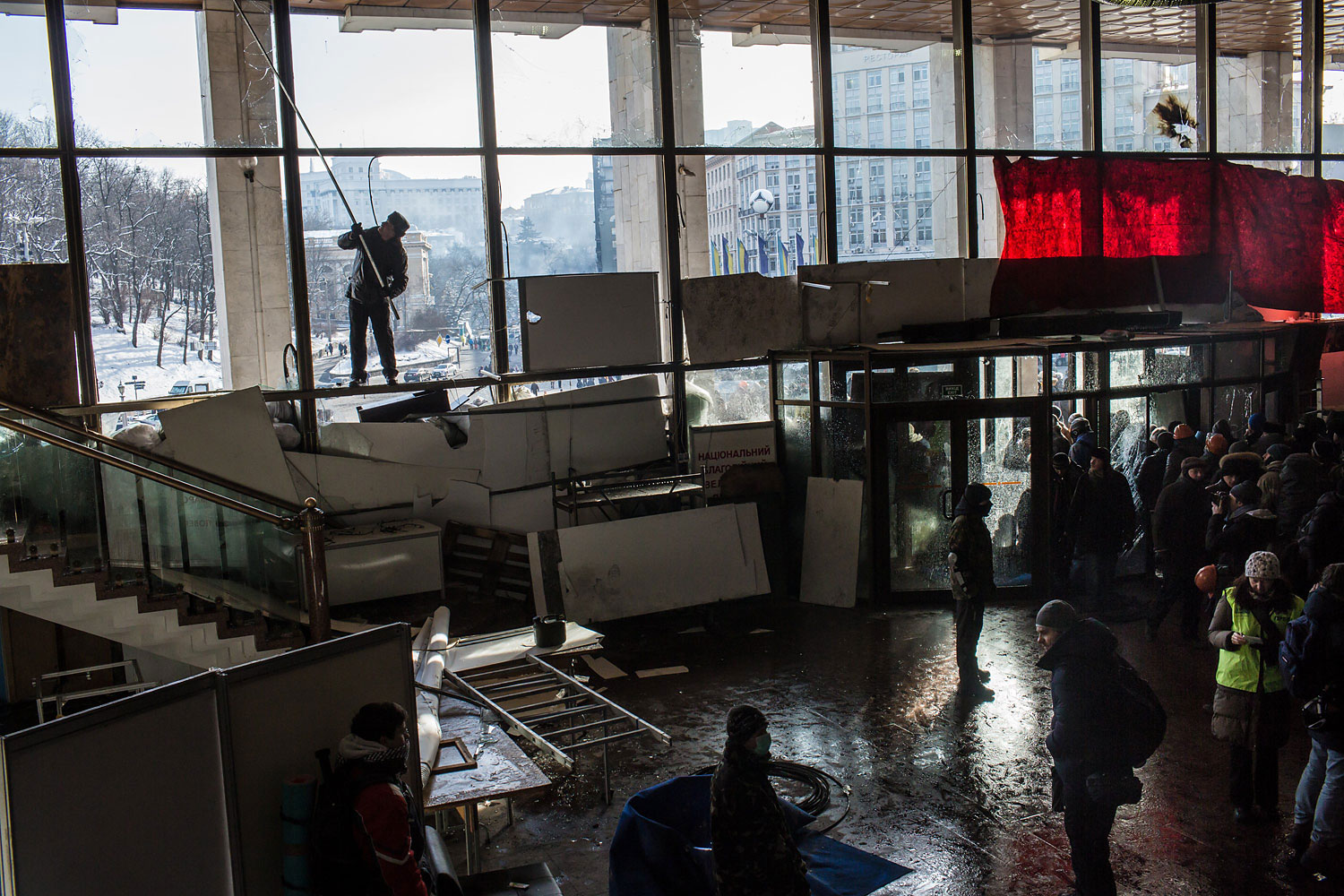A man uses a pole to remove the remains of broken windows at Ukrainian House, which was taken over by anti-government protesters on Jan. 26, 2014 in Kiev.