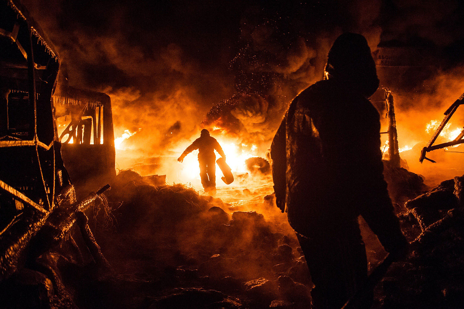 Ukrainian anti-government protesters walk past burning tyres during clashes with riot police in central Kiev early on Jan. 25, 2014.