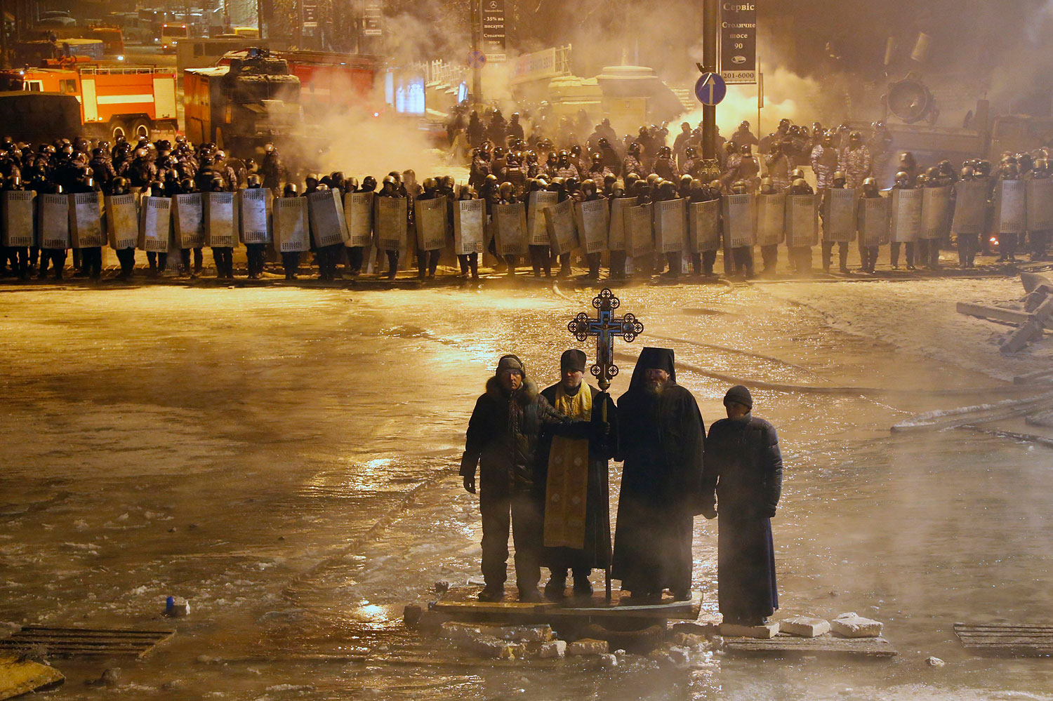 Orthodox priests pray as they stand between pro-European Union activists and police lines in central Kiev,  Jan. 24, 2014.