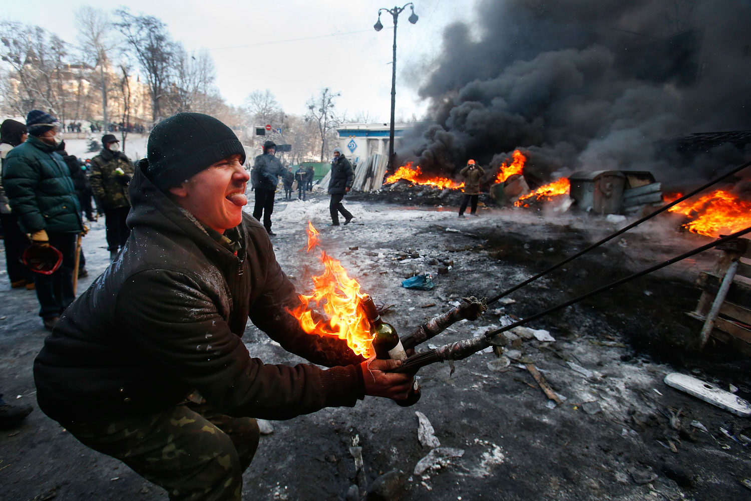 Protesters use a large slingshot to hurl a Molotov cocktail at police in central Kiev, Jan. 23, 2014.