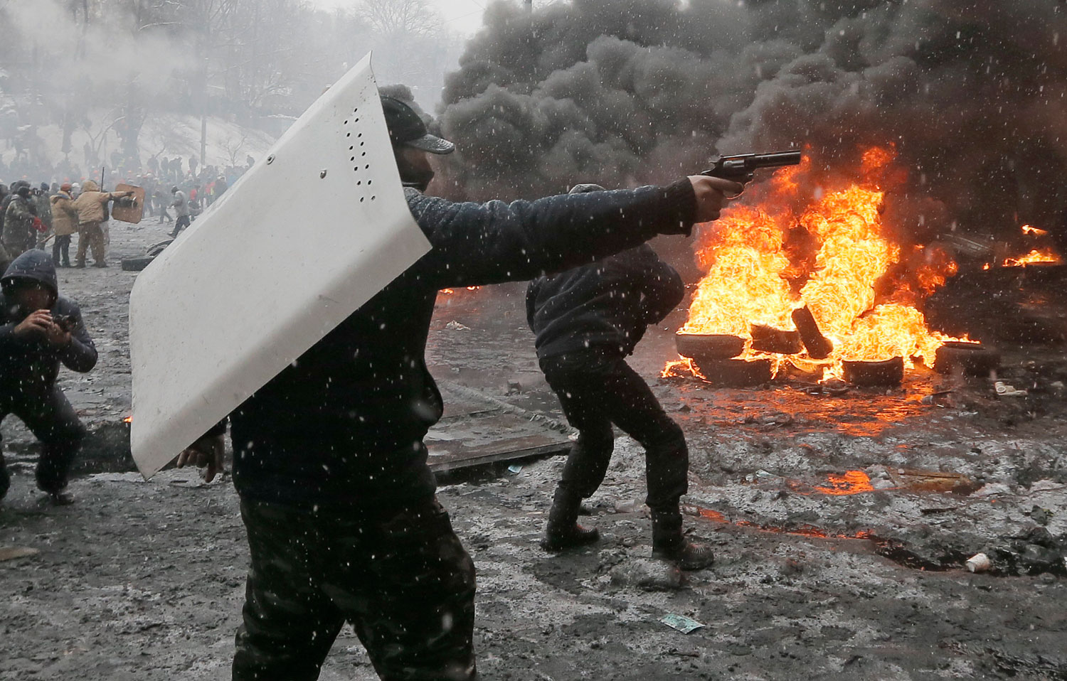 A protester points a handgun during a clash with police in central Kiev, Jan. 22, 2014.