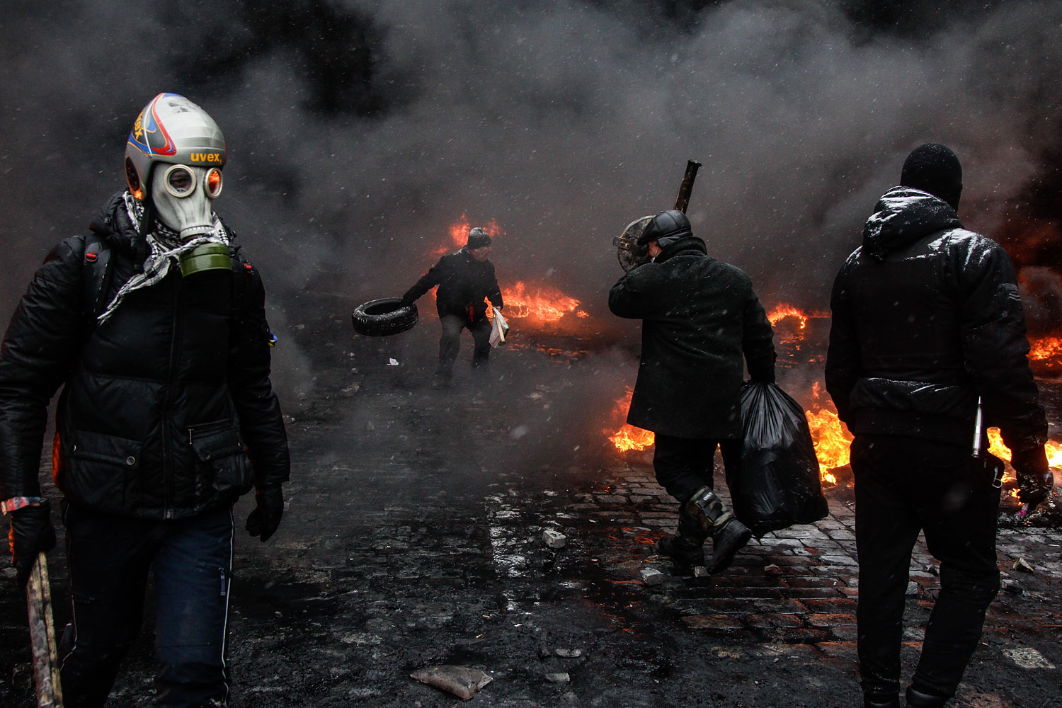 An opposition supporter wears a gas mask during clashes between riot police and anti-government demonstrators in central Kiev, Jan, 22, 2014.