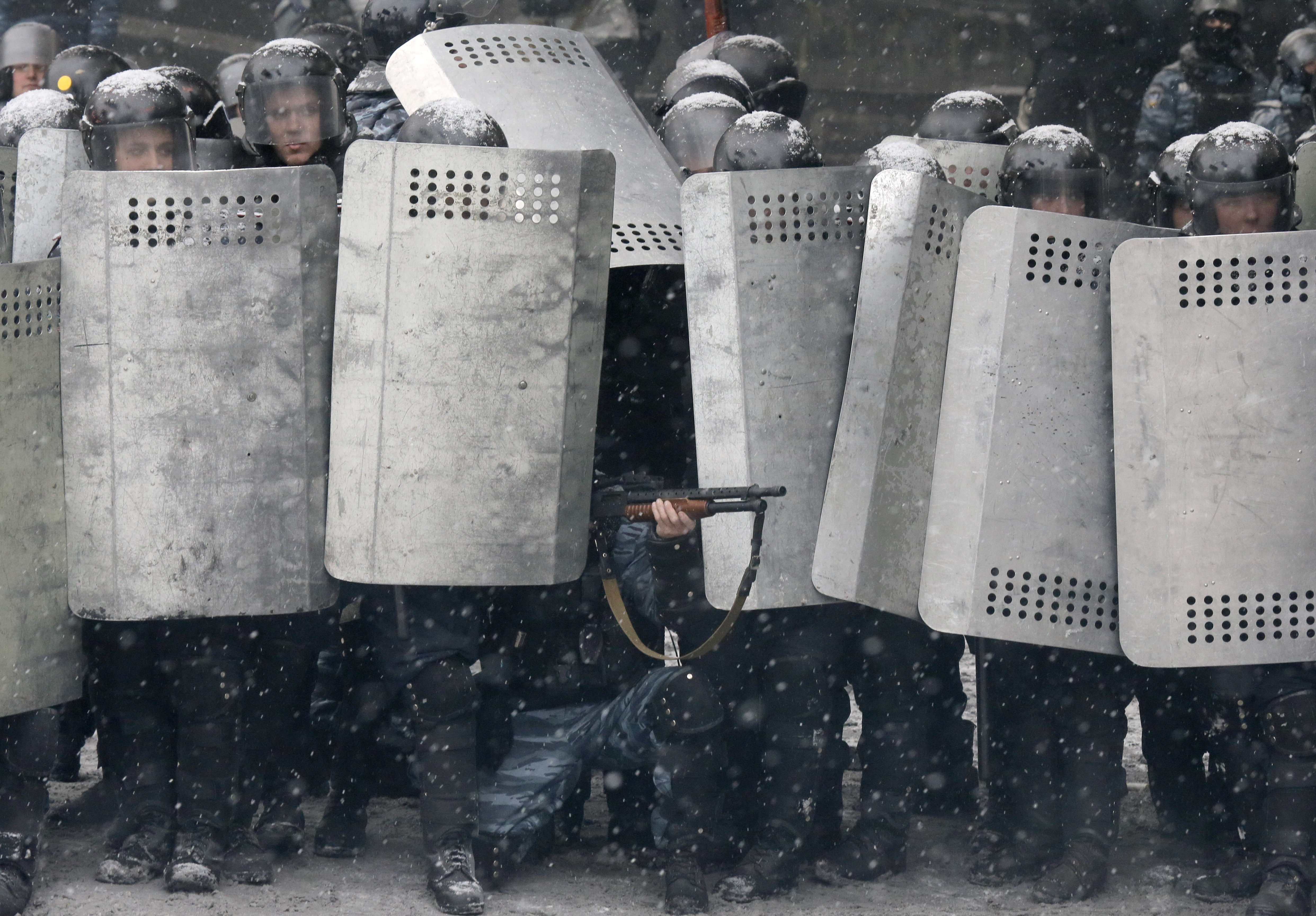 A police officer aims his shotgun during clashes with protesters in central Kiev, Jan. 22, 2014.
