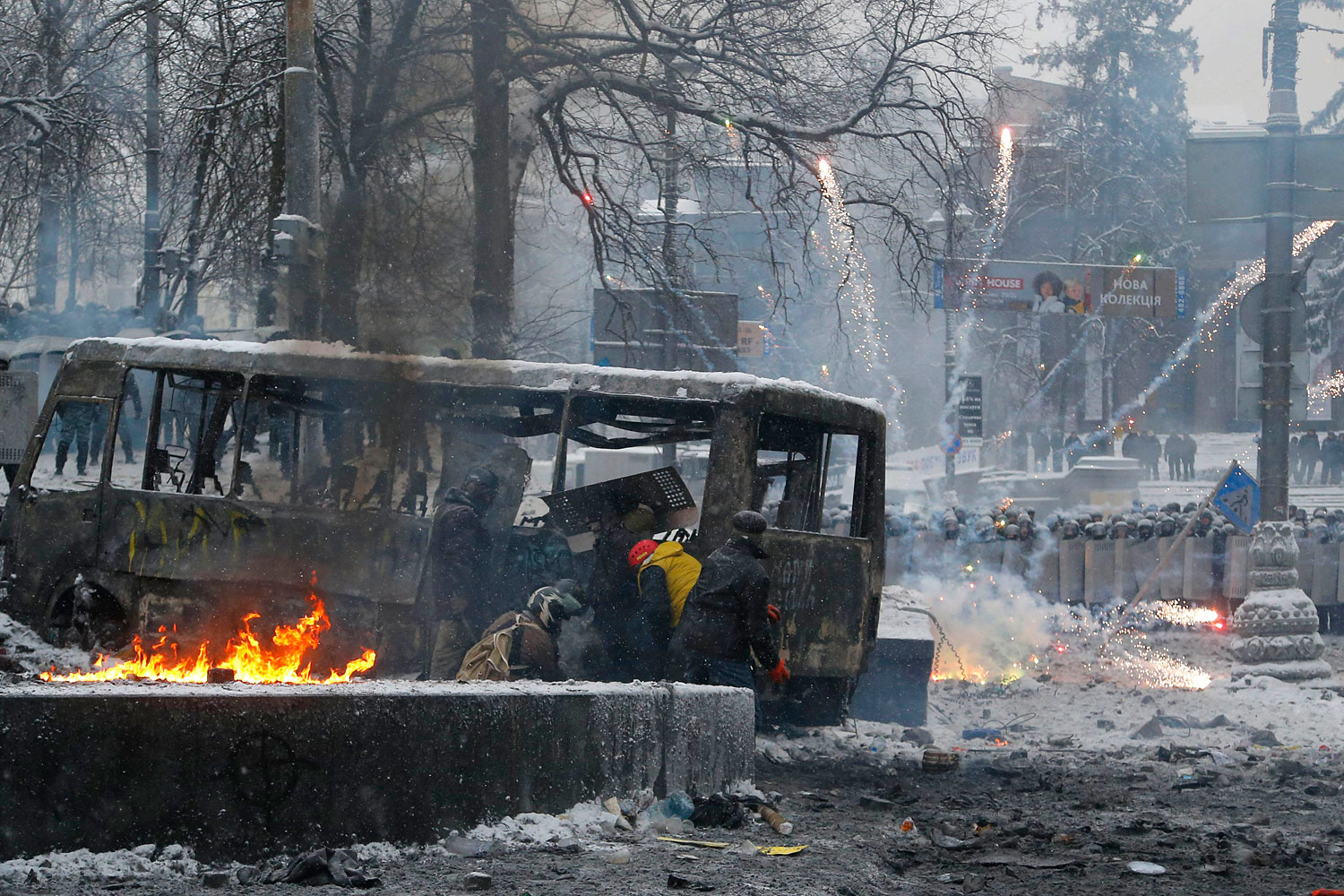 Protesters duck behind a burned vehicle as they clash with police in central Kiev, Jan. 22, 2014.