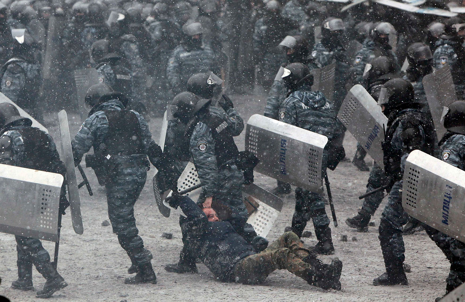 Riot police officers hold a man during clashes with pro-European protesters in Kiev, Jan. 22, 2014.
