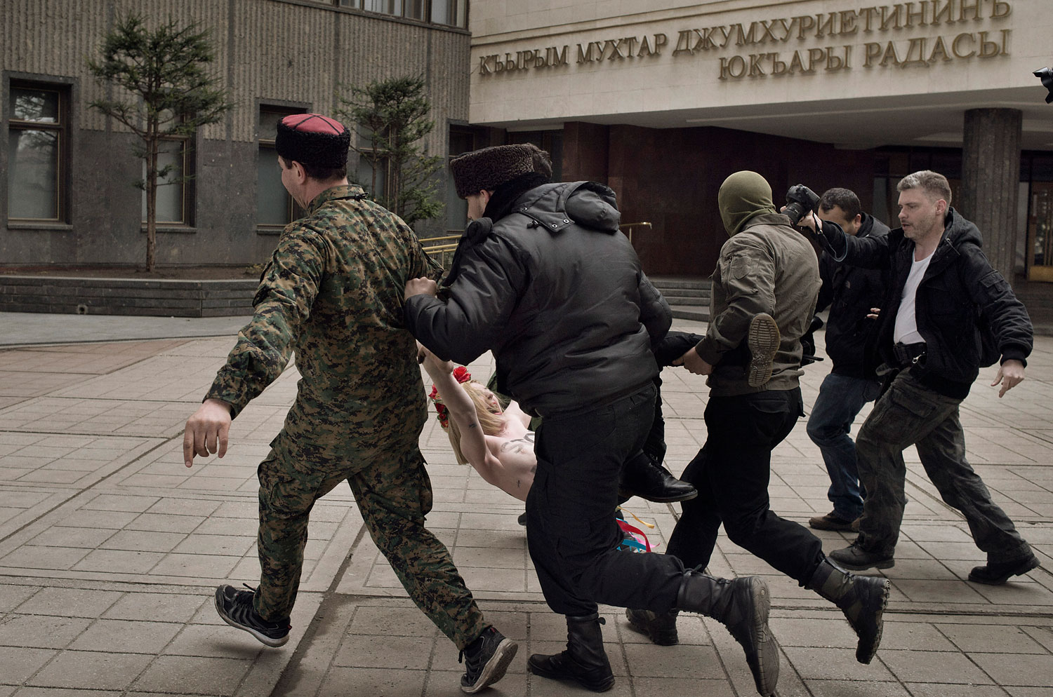 """Cossacks and Ukrainian police detain feminist protesters who interrupted a pro-Russian rally with shouts of """"Stop Putin's war"""" in Simferopol, Crimea, March 6, 2014."""