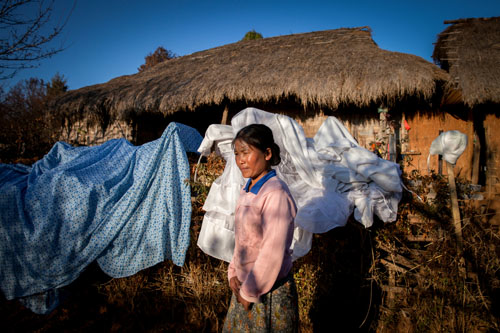 Galau Dau Yang, 35, stands outside her home in the northern Shan State village of Kut Khaing. Galau Dau Yang, who is ethnically Kachin, was gang-raped by police. Like in most conflict zones, human rights organizations report that rape is being used as a weapon by the military and police in Kachin State and neighboring Shan State, where many of the refugees have fled