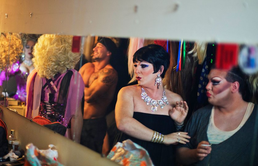 Andrei Sarkisian, second from right, who goes by the stage name of Miss Zhuzha, gets ready backstage before a performance at the Mayak cabaret in Sochi, Feb. 8, 2014.