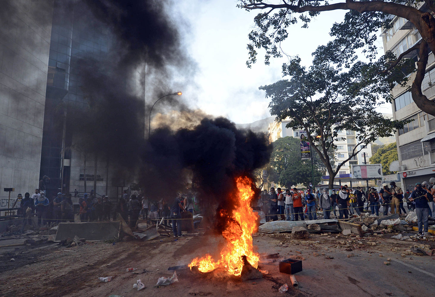 Opposition demonstrators set a fire by a barricade as they protest against the government of Venezuelan President Nicolas Maduro in Caracas on March 4, 2014.