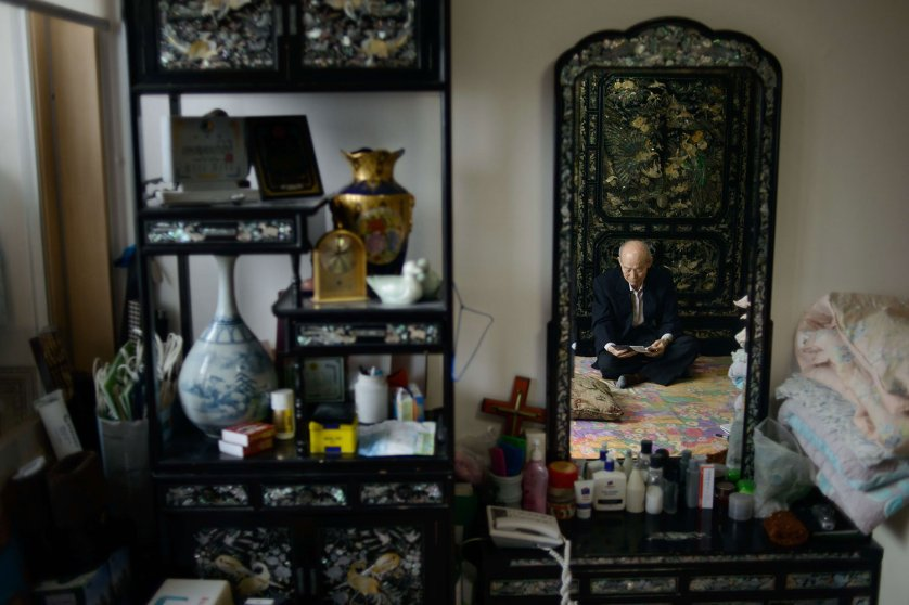 North Korean-born Kim Se-Rin sits in the bedroom of his home on the outskirts of Seoul, on Feb. 17, 2014, as he looks at photos of his South Korean family members that he plans to give to his North Korean relatives whom he had not seen for 60 years.