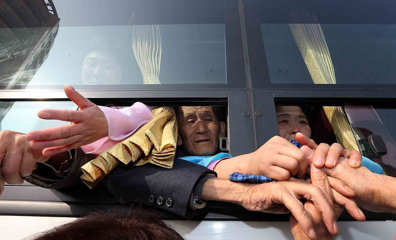 North and South Korean family hold hands at a bus as they leave after the inter-Korean family reunion meeting at Mount Kumgang resort, North Korea, Feb. 25, 2014.