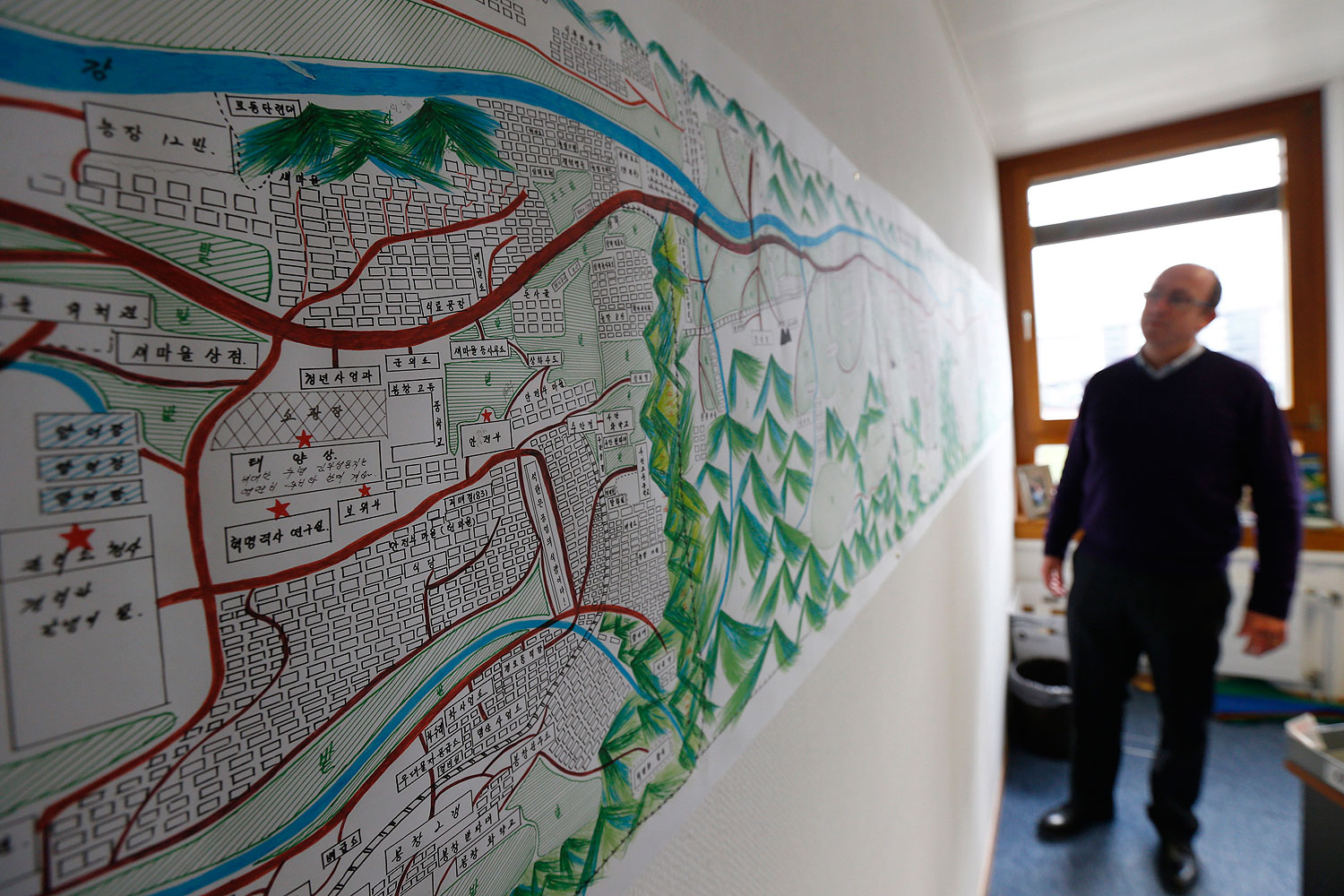 A United Nations Human Rights staff stands in front of a drawing illustrating North Korean labour camp no 18 in Geneva Feb. 17, 2014