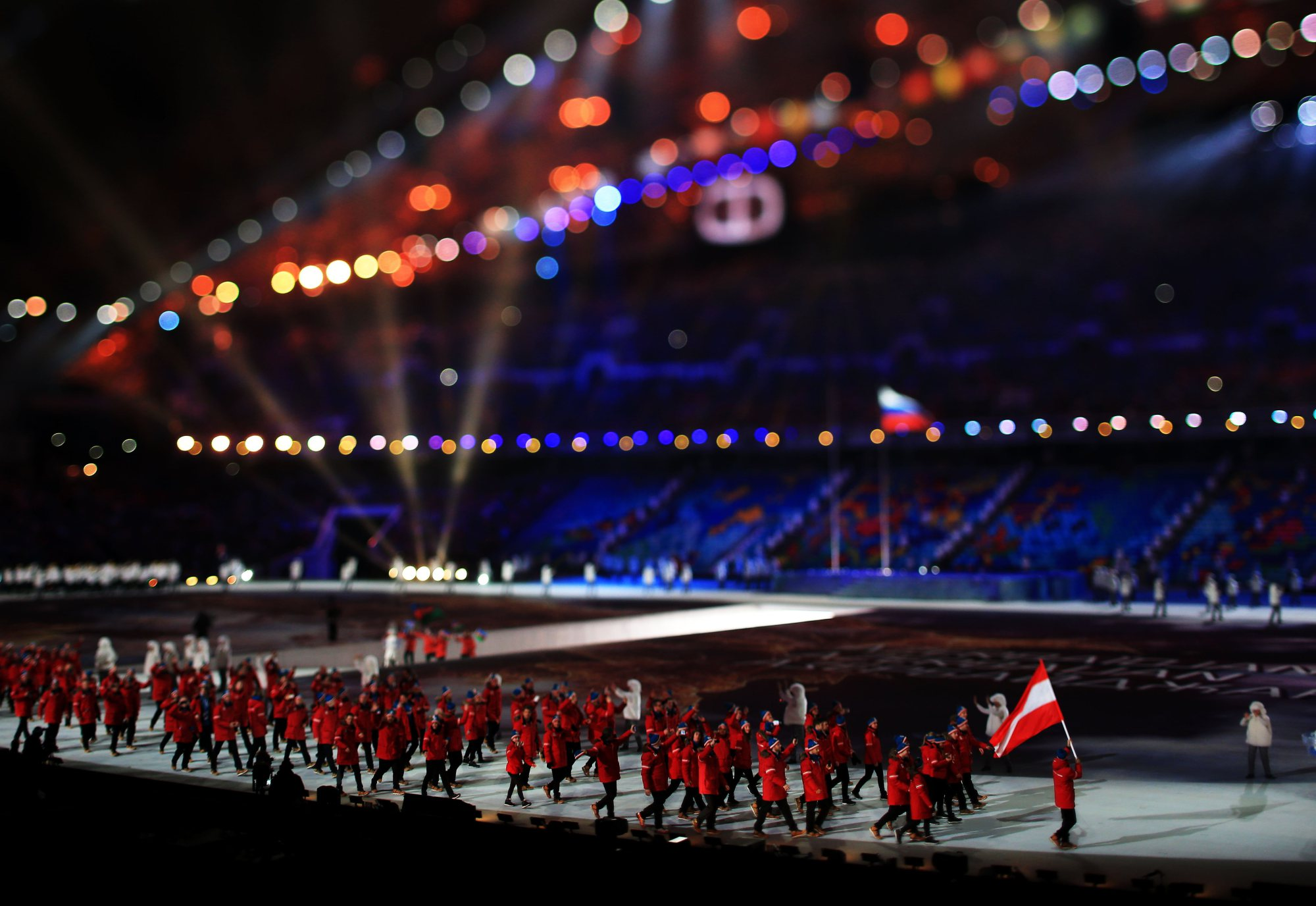 Nordic combined skier Mario Stecher of the Austria Olympic team carries his country's flag during.