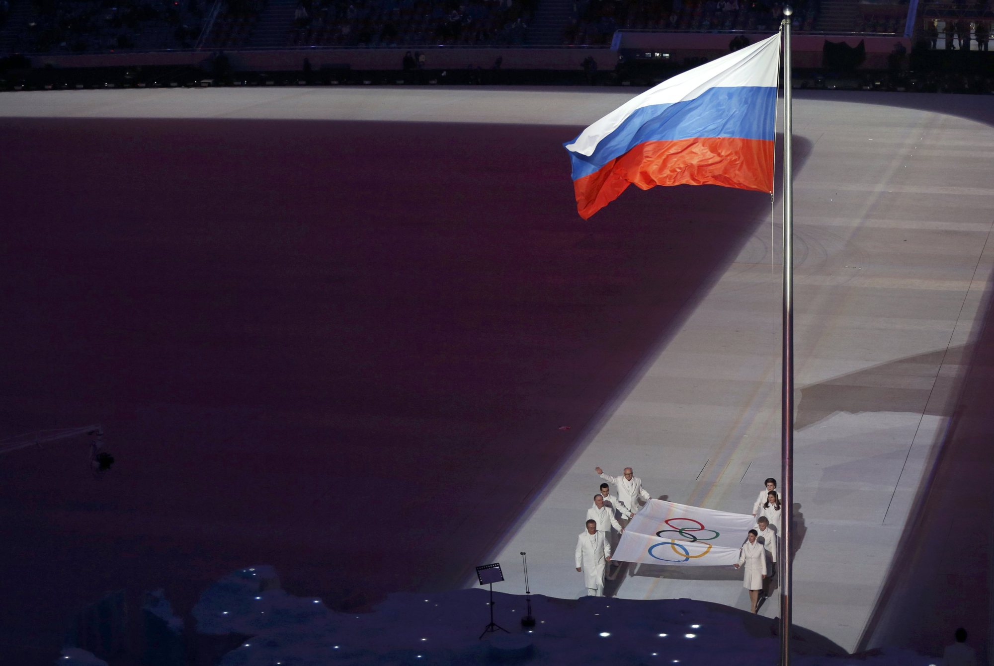 The Olympic flag is paraded past the Russian flag.