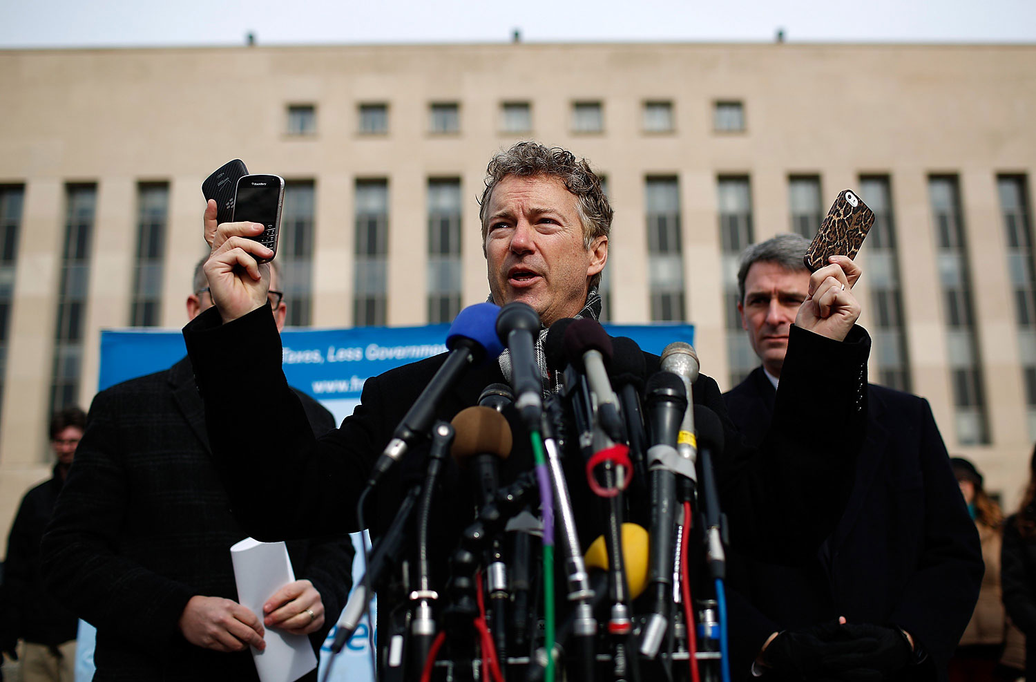 Sen. Rand Paul holds up a group of cell phones in front of U.S. District Court to announce the filing of a class action lawsuit against the administration of U.S. President Barack Obama, Feb. 12. 2014.